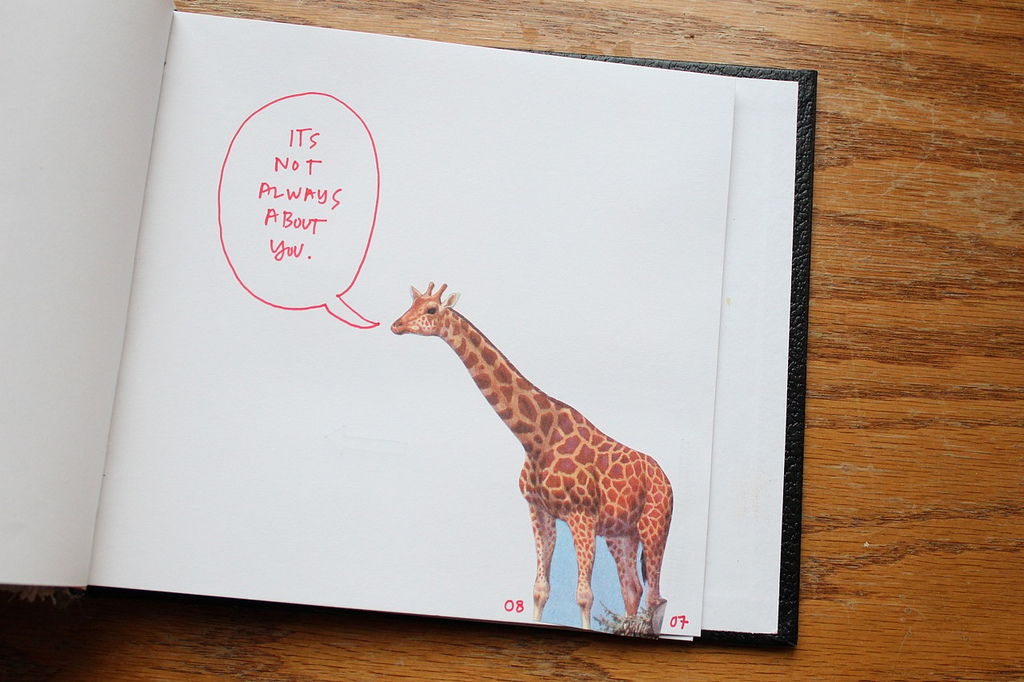 "A journal page with a giraffe on it, with a handwritten speech bubble containing the words, ""It's Not Always About You"""