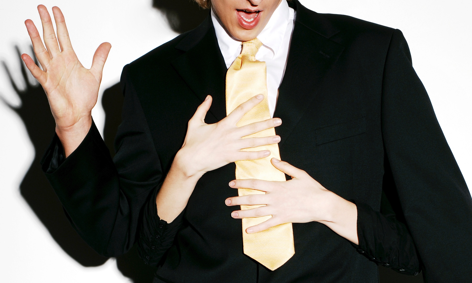 A man in a black suit, white shirt and yellow tie looking comically surprised at what look to be a woman's hands wrapped around him groping him from behind.