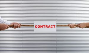 A business man and business woman playing tug-of-war with a contract.