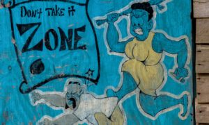 Feminism: Graffiti on a wall in Jamaica shows a woman chasing a man with a club.
