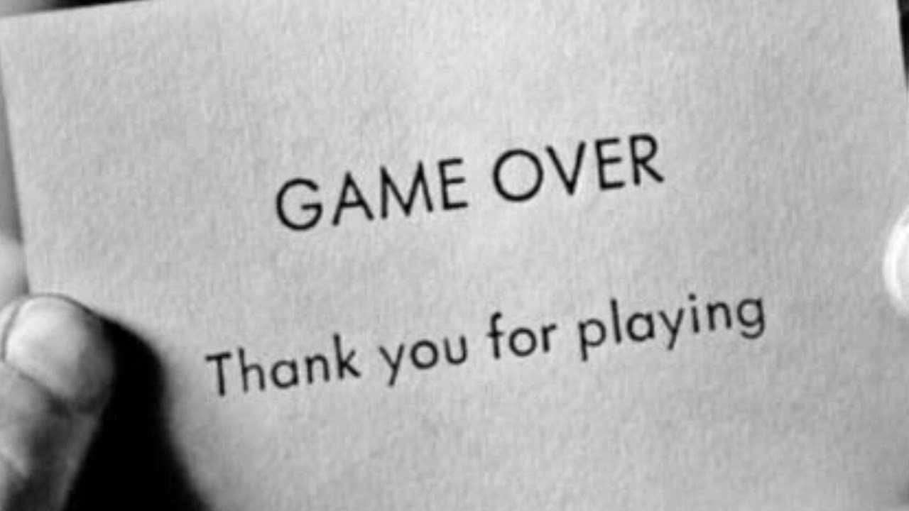 "Black and white image of hands holding a card that says, ""GAME OVER. Thank you for playing."""