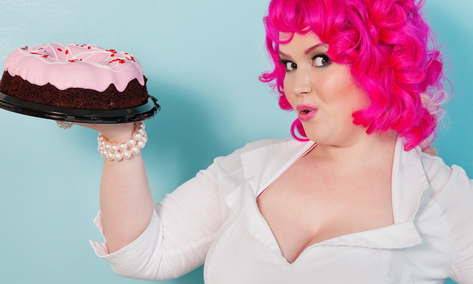 A cheeky pretty woman with hot pink hair holding a pink-frosted chocolate cake.