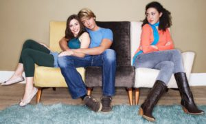 An m/w couple is cuddling on the couch, while another woman looks on with a dangerous expression.