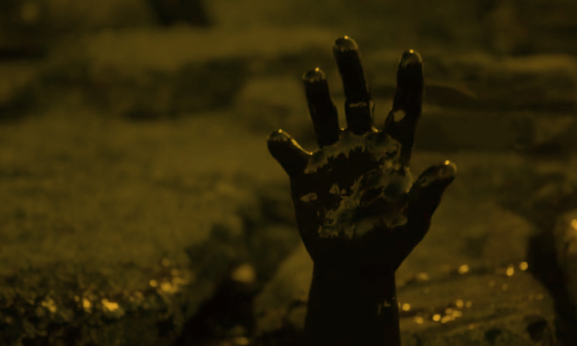 A very dark image of a hand covered in tar reaching out of a pool of tar as if for help or in it's last spasms.