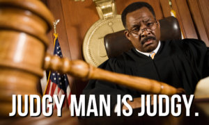 """A very concerned-looking man in a judge's robe with a gavel in the foreground. Overlaid with the words """"Judgy Man Is Judgy."""""""