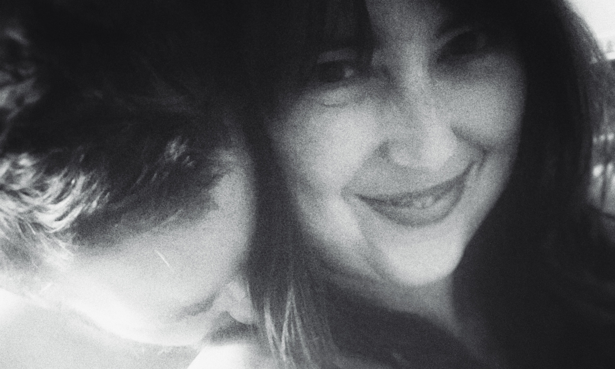 A black and white image of Pet nuzzling my neck as I smile.
