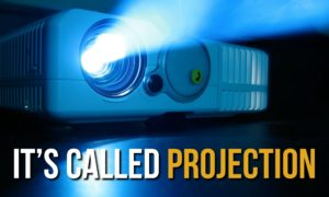 """A projector in a dark room with the words """"It'a called projection."""""""