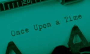 """A piece of paper in a typewriter with the words, """"Once Upon a Time."""""""