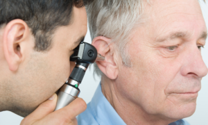 An image of one man peering into another man's ear.
