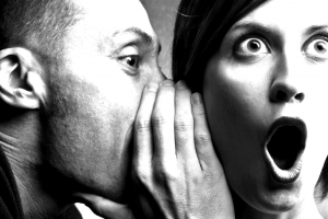 A man whispering into someone's ear. They look shocked.