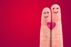 Two fingers together, with little people drawn on them, and a heart joining them.