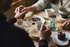 An man and a woman holdinghands across a table filled with coffee, cupcakes and soup.