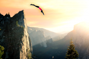 A high cliff, with a beautiful sunrise and a diver flying off.