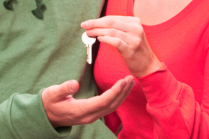A person in a red sirt hands keys to a person in a green shirt.