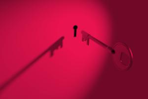 A dramatic photo of a key nearing a keyhole.