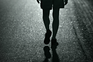Feet and legs walking away on a road.